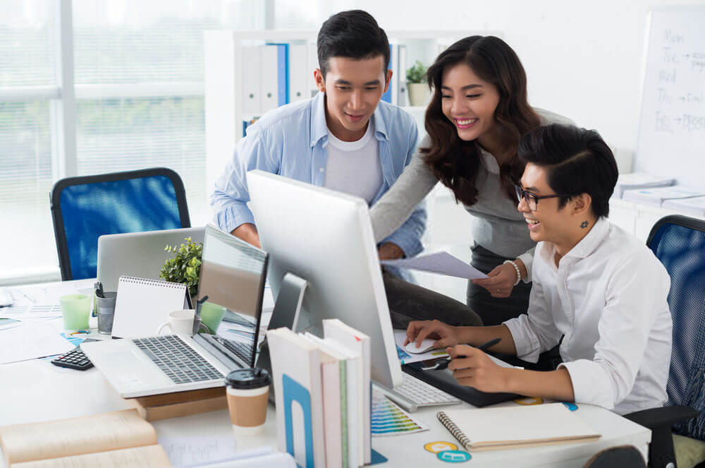 group of workers smiling staring at monitor