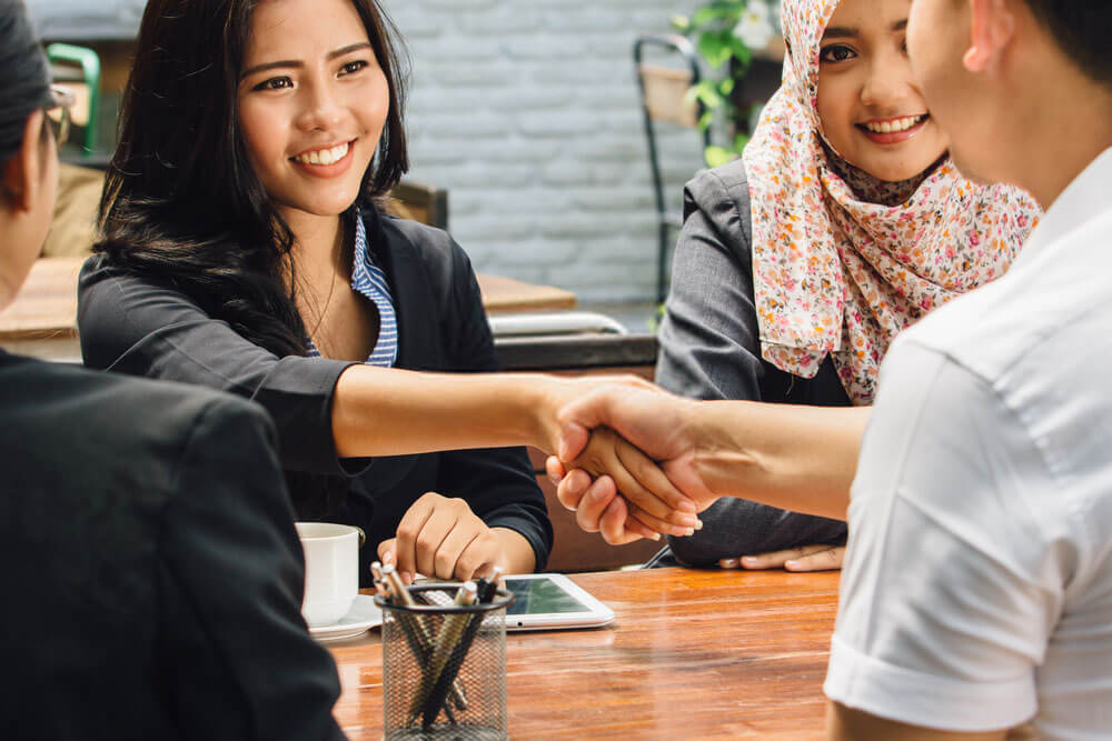 man and woman shaking hands on discussion