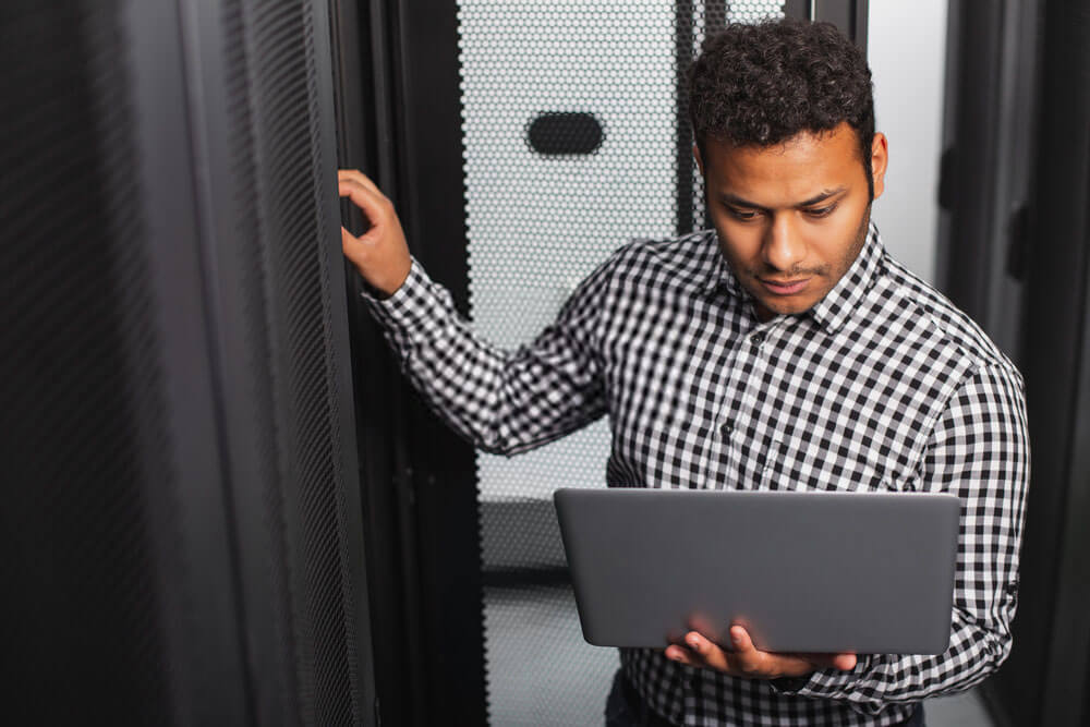 man with his laptop at the server room